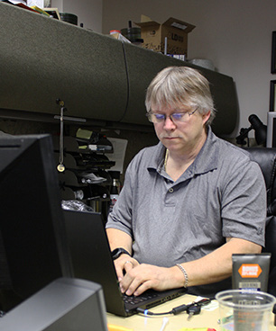 Steve Hamilton works on one of the many computers that come in to the IT department for repairs.