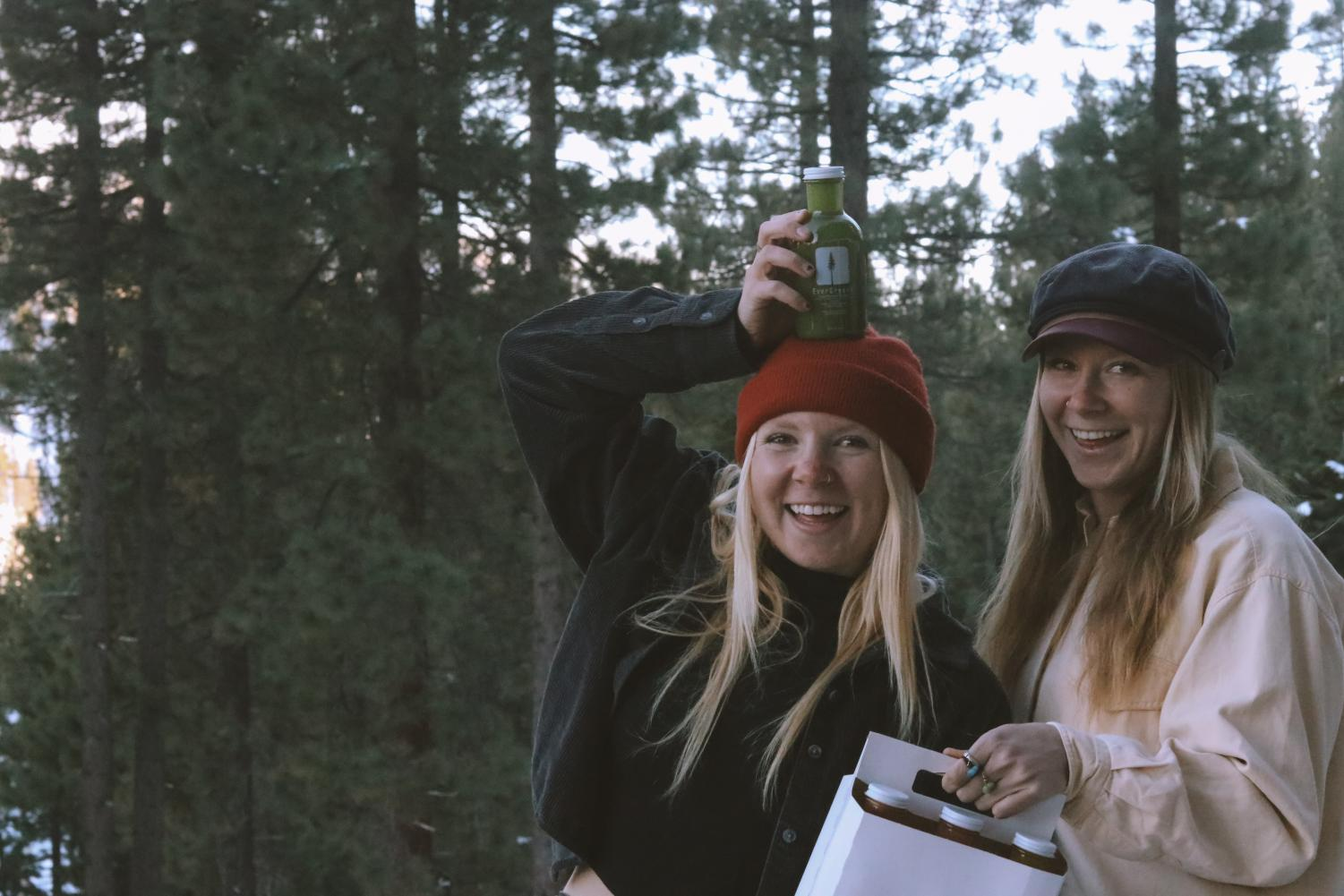 SNU students and sisters Emme and Maea Wistrom pose in the evergreens with an EverGreens juice six-pack.